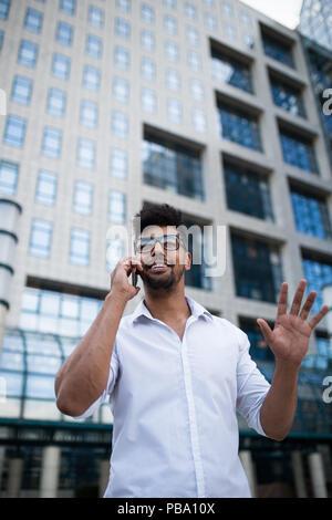 Junge hübsche Afro-amerikanische Mann stand vor der riesigen, modernen business Gebäude; lächelnd und Gespräch am Handy. - Stockfoto