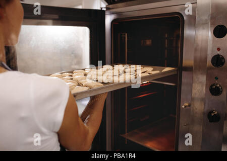 Frau Baker, ein Backblech voller Brötchen in den Ofen. Frau backen Brötchen in einer Bäckerei. - Stockfoto