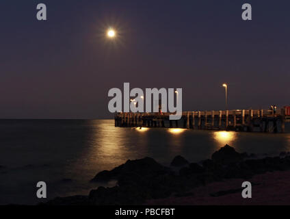 Palm Cove Anlegesteg am Abend, LE kurz nach Sonnenuntergang als der Vollmond steigt Offshore und schafft eine glitzernde Pfad auf dem Wasser - Stockfoto
