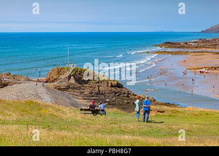Vom 6. Juli 2018: Bude, Cornwall, UK-Touristen auf Kompass Hügel hinunter über besetzt Summerleaze Strand während der Sommerhitze, als Menschen aus, die in kühlen