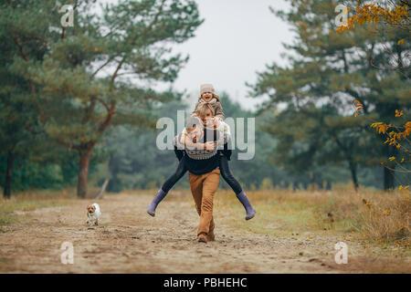 Glückliche Familie hat Spaß und Mann seine Frau und seine Tochter trägt auf seinem Rücken im Wald Weg neben Hund beim Spaziergang im Wald. - Stockfoto