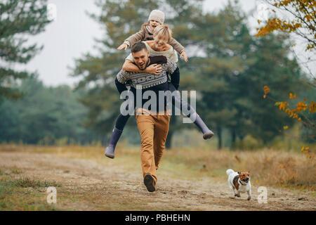 Glückliche Familie hat Spaß und Mann seine Frau und seine Tochter trägt auf seinem Rücken im Wald Weg neben Hund beim Spaziergang im Wald. Nahaufnahme. - Stockfoto