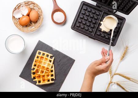 Foto oben von Mehl, Eier, Waffeleisen, ährchen, frisch gerösteten Waffeln, menschliche Hände - Stockfoto