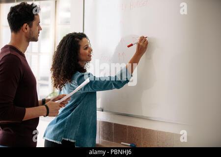 Büro Kollegen diskutieren monatlichen Budgets und Pläne auf einer Tafel. Geschäftsfrau, die an die Tafel schreiben, während ihr Kollege ein Papier in der Hand hält. - Stockfoto