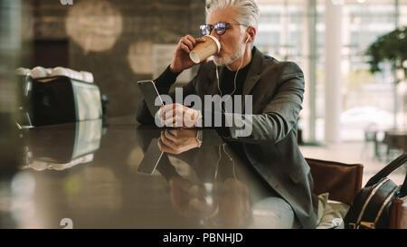 Mitte der erwachsenen Geschäftsmann in einem Cafe sitzen und Kaffee trinken mit Smart Phone. Kaukasische Mann in Kopfhörer an seinem Handy in Coffee Shop suchen. - Stockfoto