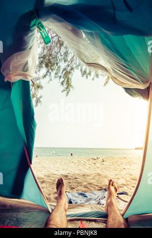 Ansicht aus einem Zelt am Strand, menschlichen Beinen in touristische Hütte liegt mit Blick auf das Meer, Kreta, Griechenland. - Stockfoto
