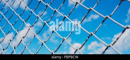 Ein Zaun aus Drahtgeflecht, Verrechnung mit Weiß auf dem Hintergrund der blauen Himmel und Sonnenschein - Stockfoto