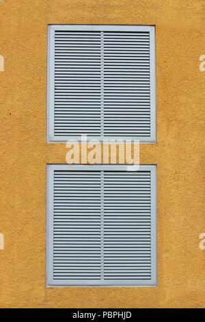 Zwei Fenster in einem großen industriellen Einkaufszentrum geschlossen mit externen Jalousie in Form von lüftungsgittern. gelb orange beige Hintergrund, rel - Stockfoto