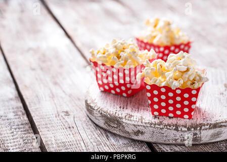 Popcorn in red Polka Dot pack auf hellem Holztisch. Selektiver Fokus - Stockfoto