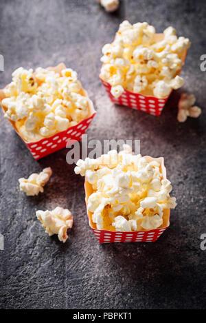 Popcorn in red Polka Dot pack auf schwarzem Beton Tabelle. Selektiver Fokus - Stockfoto