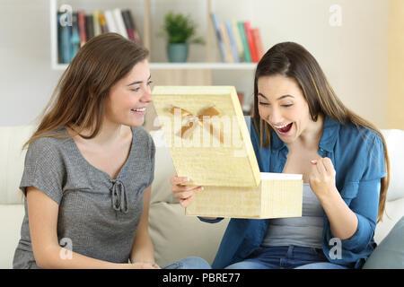 Aufgeregt Frau ein Geschenk von einem Freund auf einer Couch im Wohnzimmer zu Hause sitzen - Stockfoto