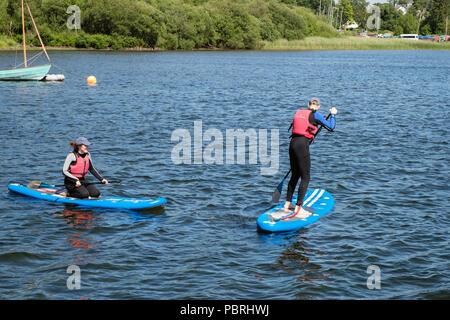 Menschen tragen Neoprenanzüge und Schwimmwesten paddleboarding auf Derwent Water in Lake District National Park. Nichol Ende, Keswick, Cumbria, England, Großbritannien - Stockfoto