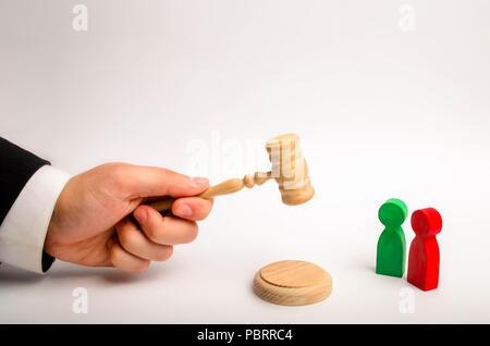 Die Hand des Schiedsrichters hat einen Hammer und ein Urteil im Streit zwischen den roten und grünen Gegner. Gerichtsverfahren, die Beilegung von Streitigkeiten und - Stockfoto