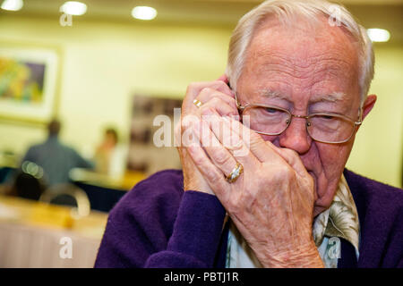 Miami Florida Downtown Hilton Hotel Handy deckt Mund Privatsphäre älterer Mann hören - Stockfoto