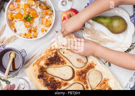 Sweet, baked Kürbis und Kuchen mit Birne. Herbst Abendessen für die ganze Familie. Kinder, die Hände im Rahmen. Kopieren Sie Raum, - Stockfoto