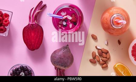 Zwei Gläser mit bunten Smoothies mit Gemüse, Beeren, Nüsse und Trinkhalm auf farbigem Papier Hintergrund - Stockfoto