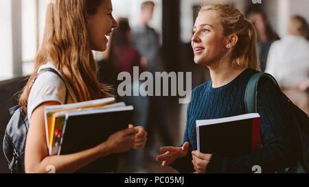 Lächelnde Mädchen in der High School Flur. Zwei weibliche Studenten im Gespräch nach dem Vortrag. - Stockfoto