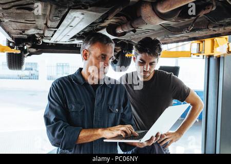 Automechaniker mit Laptop im Auto Reparatur Service mit Kollegen stehen. Auto Service Professionals mit Laptop, während das Auto untersuchen. - Stockfoto