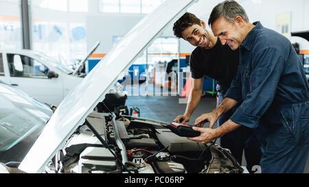 Zwei glückliche Kfz-mechaniker tun auto motor Überprüfung mit einem Gerät. Mechanik Diagnose eines Auto Service Station. - Stockfoto