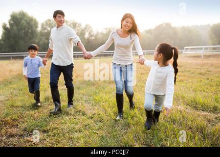 Fröhlicher junger chinesischen Familie zu Fuß auf Wiese - Stockfoto