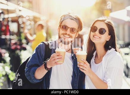 Zwei attraktive besten Freunde in Sonnenbrille Walking im Freien an der sonnigen Sommer Straße und trinken Kaffee - Stockfoto