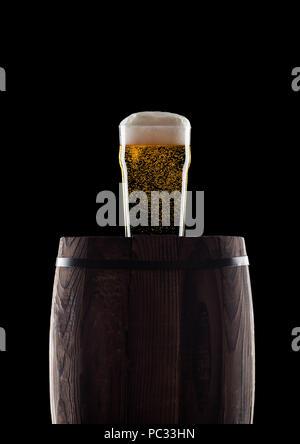 Kalten Glas Handwerk Bier auf alten Holzfass auf schwarzem Hintergrund mit Tau und Blasen - Stockfoto