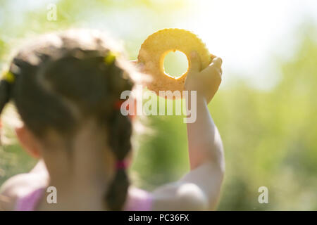 Das Mädchen durch das Loch im Brot schaut auf die Sonne am Himmel. - Stockfoto