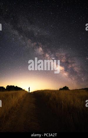 Ein Mann steht auf einem Feldweg in einem Feld bis in den Nachthimmel, Sterne und die Milchstraße in der Nähe von Lake Sonoma, Kalifornien. - Stockfoto