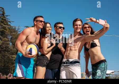 Ferien, Sommer, Freundschaft, Technologie und Personen Konzept - Gruppe der lächelnden überglücklich Freunde, in Badebekleidung am Strand gekleidet, selfie - Stockfoto