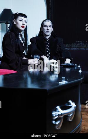 Eine gotische Paar in ihren Wohnzimmer in Ihrem Hause zu sitzen. Der Couchtisch ist in der Tat ein Sarg. - Stockfoto