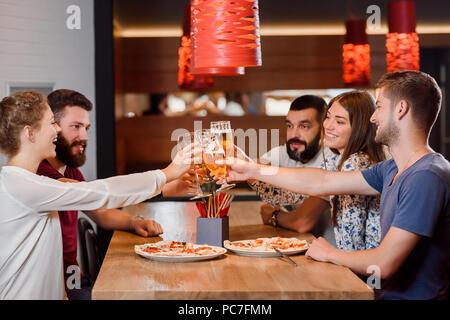 Eine Gruppe von fünf Freunden in der modernen Pizzeria oder Cafe sitzen und Spaß haben. Frauen und Männer, die ihre Gläser leckeres Bier klirren. Sie haben auch zwei leckere Pizza auf Holztisch. - Stockfoto