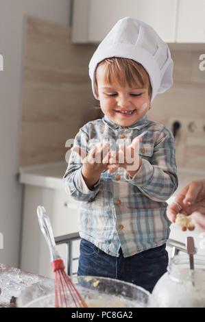 Adorable kleine Zicklein in Koch hat mit Blick auf die schmutzigen Hände mit Mehl beim Kochen - Stockfoto