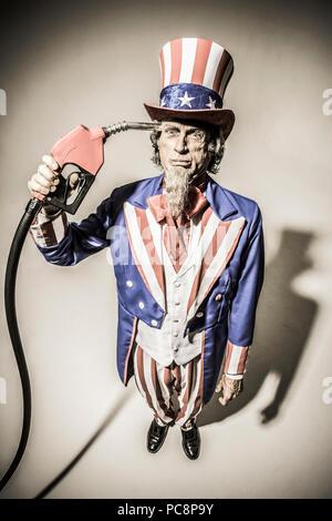 Uncle Sam stehend mit einer Gaspumpe nozzel vor ihm statt. Konzeptionelle Schuß mit der Darstellung der Amerikanischen Abhängigkeit vom Öl/Gas/Öl. - Stockfoto