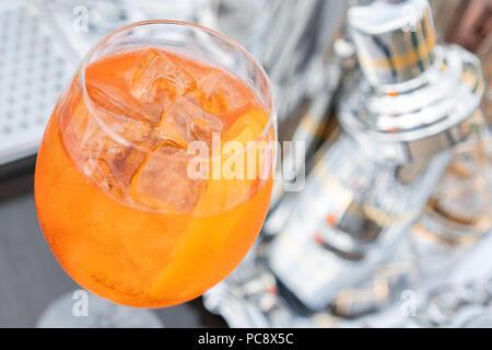 Aperol Spritz Cocktail im Beschlagenen Glas, selektiven Fokus. Alkoholische Getränk auf Theke mit Eiswürfeln und Orangen. metall Shakers im Hintergrund - Stockfoto