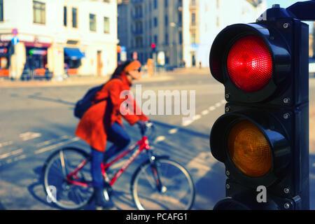 Mädchen im roten Mantel mit dem Fahrrad an der Kreuzung der Stadt für eine rote Ampel im Frühling - Stockfoto
