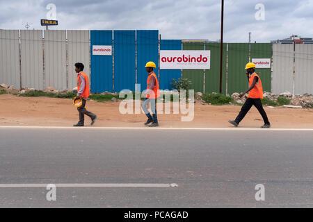 Indischer Bauarbeiter tragen Schutzhelm Spaziergang auf der Straße mit Blick auf Ikea im Hintergrund in Hyderabad, Indien. - Stockfoto