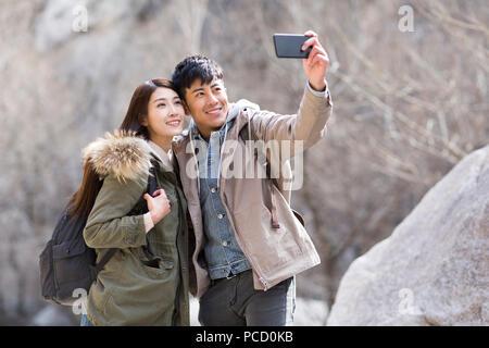 Glückliche junge chinesische Paar unter selfies im Winter - Stockfoto