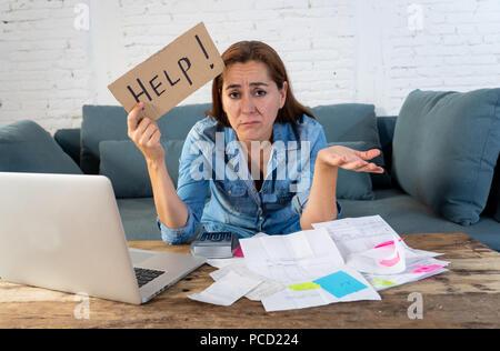 Portrait von besorgt verzweifelte Mutter Frau Gefühl hervor, während sie durch Finanzen mit Laptop und Rechner im Wohnzimmer in zahlt sich aus Deb arbeiten - Stockfoto