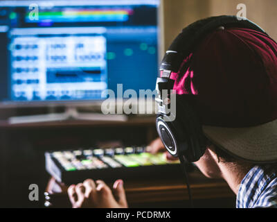 """Rückansicht der Toningenieur in """"SNAPBACK"""" und halten Sie die Kopfhörer auf dem Kopf überwachung Musik im Studio - Stockfoto"""
