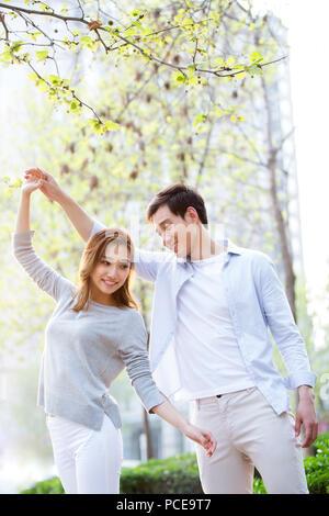 Glückliche junge chinesische Paare tanzen im Freien - Stockfoto