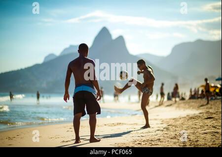 Nicht erkennbare junge Brasilianer spielen Sie eine Partie Fußball Keepy Uppy'-altinho' am Ufer des Ipanema Beach. - Stockfoto