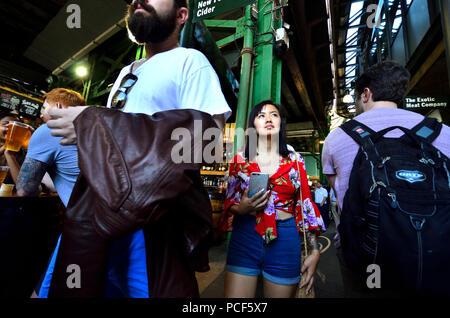 Asiatische Tourist in einem überfüllten Borough Markt, Southwark, London, England, UK.