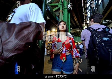 Asiatische Tourist in einem überfüllten Borough Markt, Southwark, London, England, UK. - Stockfoto