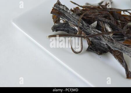 Blick von oben auf die getrockneter Seetang Detail: Wakame. Auf weiß isoliert. Nährstoff reichen vegan, roh und gesunde Gemüse. - Stockfoto