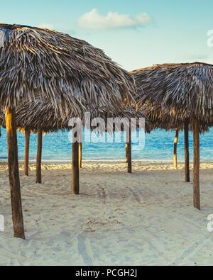 Gruppe Reihe vieler Thatch attap Stroh Sonnenschirme deckt, stehend auf meer ozean Strand bei Sonnenuntergang, getönt mit Filtern in Retro Vintage film Stil, Sommer - Stockfoto