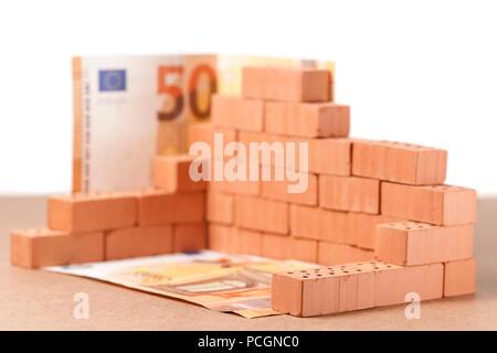 Low Angle View gestapelt Spielzeug Brick Building Block mit 50 Euro Rechnungen an der Ecke und Masse auf auf Hartfaser gegen den weißen Hintergrund. - Stockfoto
