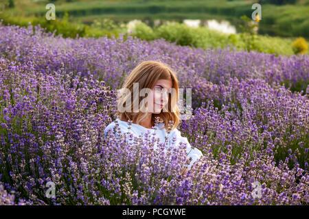 Junge Mädchen in weißem Kleid sitzt in Lavendelblüten und Lächeln - Stockfoto