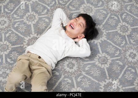 Gerne Chinesisch kleiner Junge auf dem Teppich liegend - Stockfoto