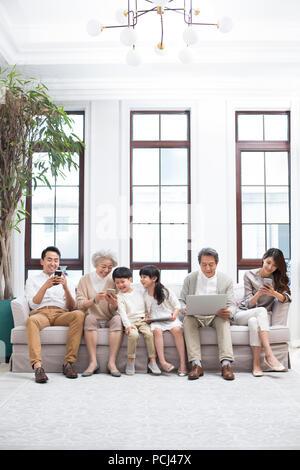 Happy chinesischen Familie mit digitalen Geräten auf Sofa - Stockfoto