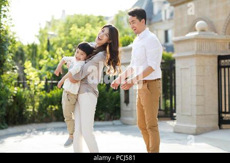 Glückliche junge chinesische Familie spielen im Freien - Stockfoto